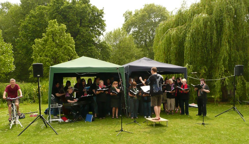 Choir members singing in the park with microphones, speakers, piano and pedalling