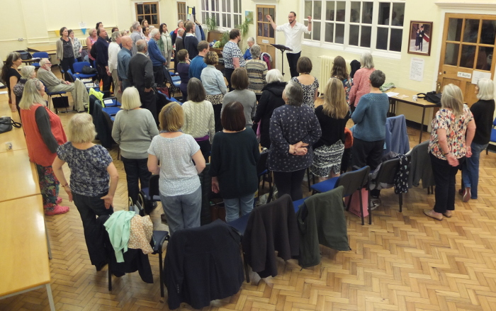 About 60 people at a rehearsal